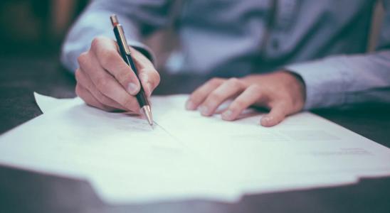 Mand der skriver på hvidt papir